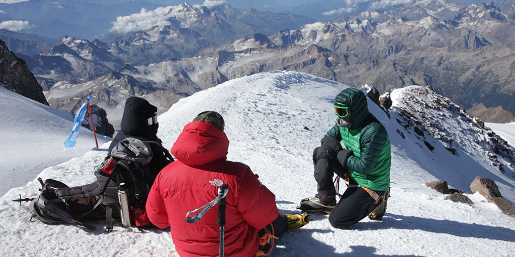 Three medical student on the summit ridge of Mount Elbrus discussing next steps.
