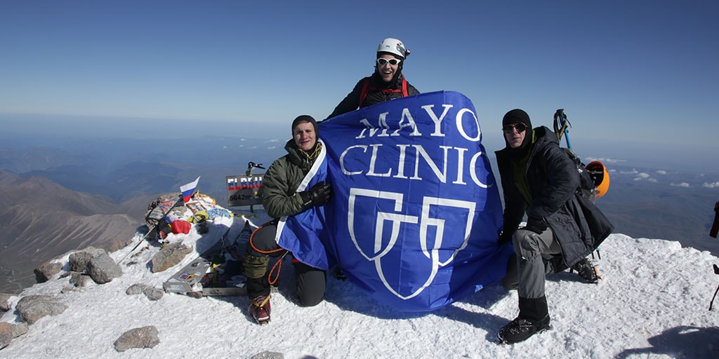 Three medical students holding Mayo Clinic flag atop Mount Elbrus