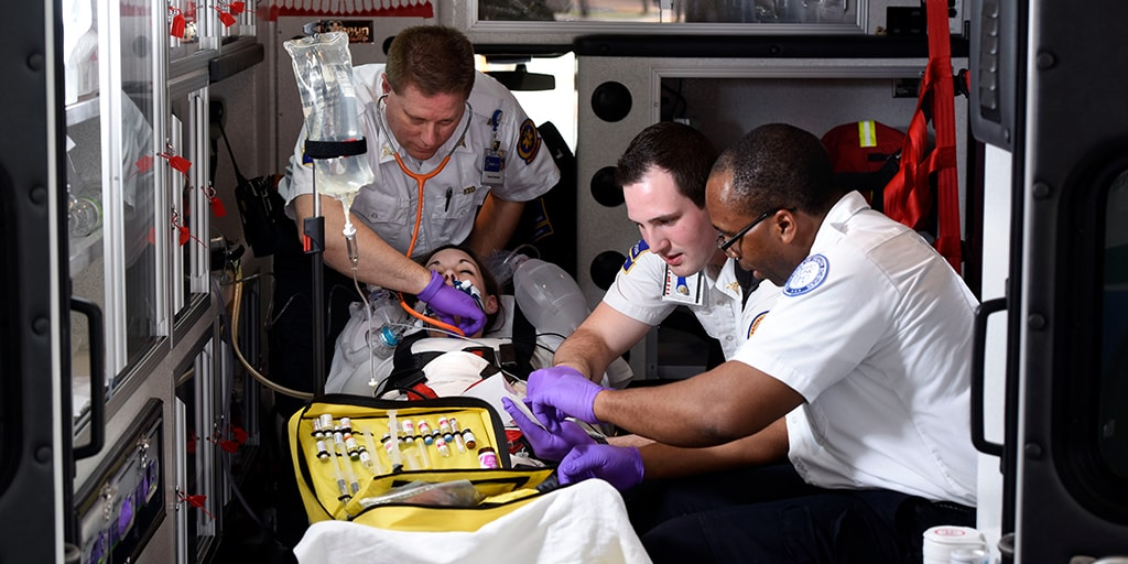 Three paramedics providing emergency care in the back of an ambulance as part of simulated educational opportunity at Mayo Clinic College of Medicine and Science