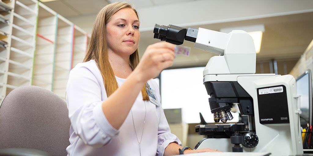 Mayo Clinic cytotechnology student preparing a specimen slide under a microscope