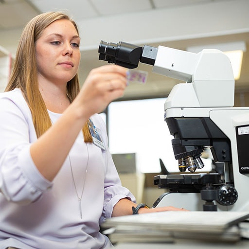 Mayo Clinic cytotechnology student reviewing specimens using a microscope