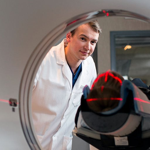Mayo Clinic health sciences student placing a patient in an imaging scanner