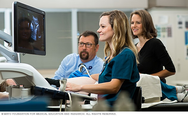 Sonography student using ultrasound to scan a patient as instructors look on