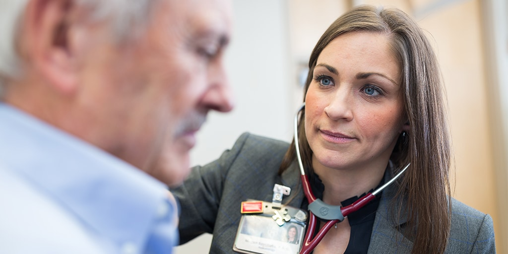 Physician Assistant wearing a stethoscope performing exam and checking heart beat of patient