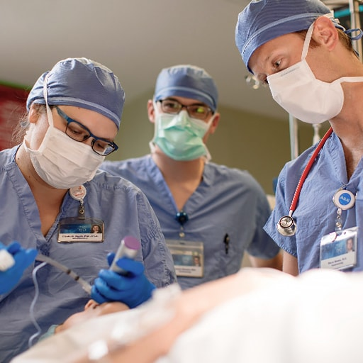 Three neuroanesthesiologists work on a patient.