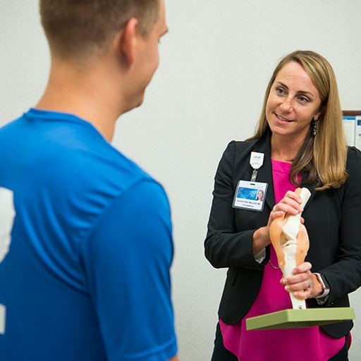 Primary Care Sports Medicine fellow speaking with a patient holding a model.