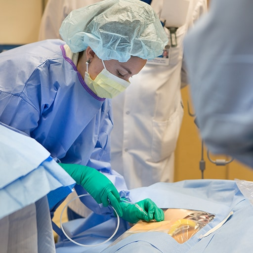 Surgical critical care fellows perform a procedure