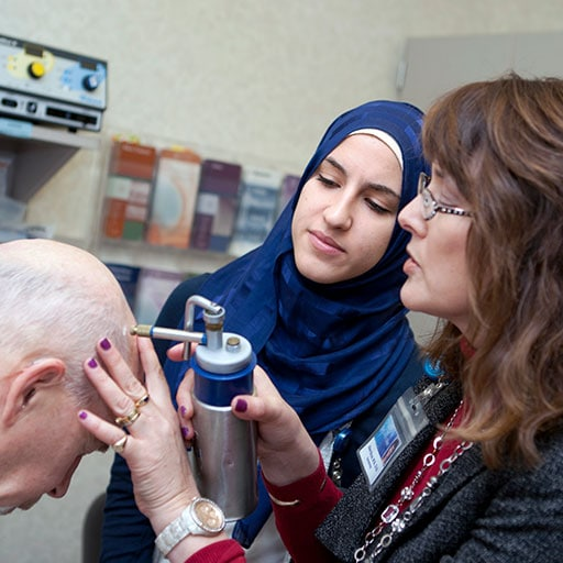 Mayo Clinic M.D. Program student observing faculty member completing a dermatology procedure
