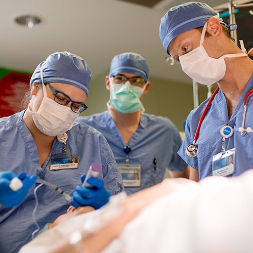Anesthesiologists performing a procedure on a mannequin
